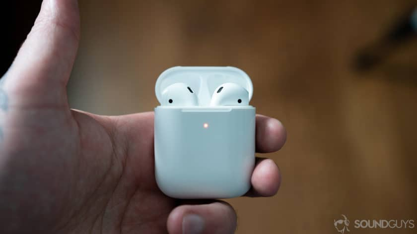 A picture of the AirPods 2 in wireless charging case held by man's hand.
