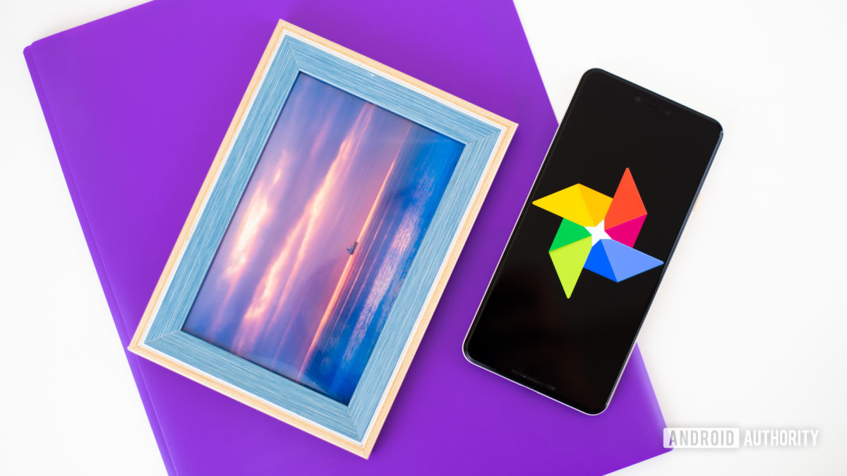 Google Photos logo on smartphone next to imaging accessories stock photo 2