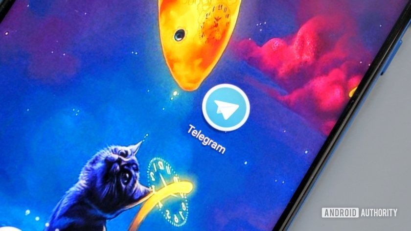 The Telegram icon on an Honor View 20 on a blue background with a cat and a fish.