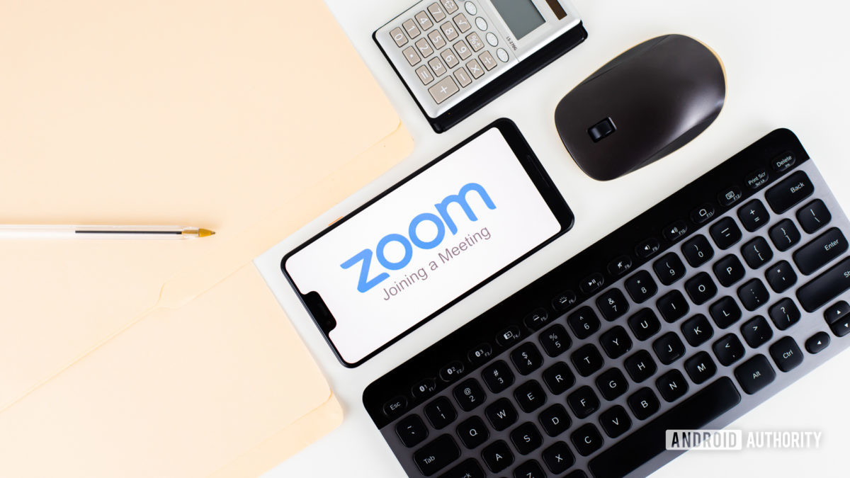 Zoom Meetings on smartphone next to office equipment stock 2
