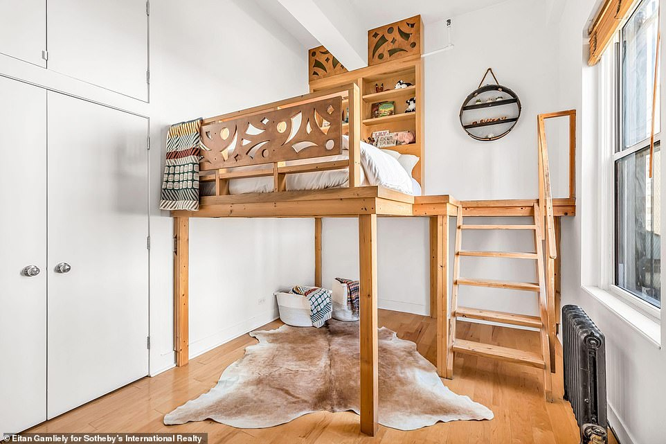 So cool: One bedroom featured an elevated bed wooden bed frame with stairs leading up to, the perfect way to enjoy the city views from the window