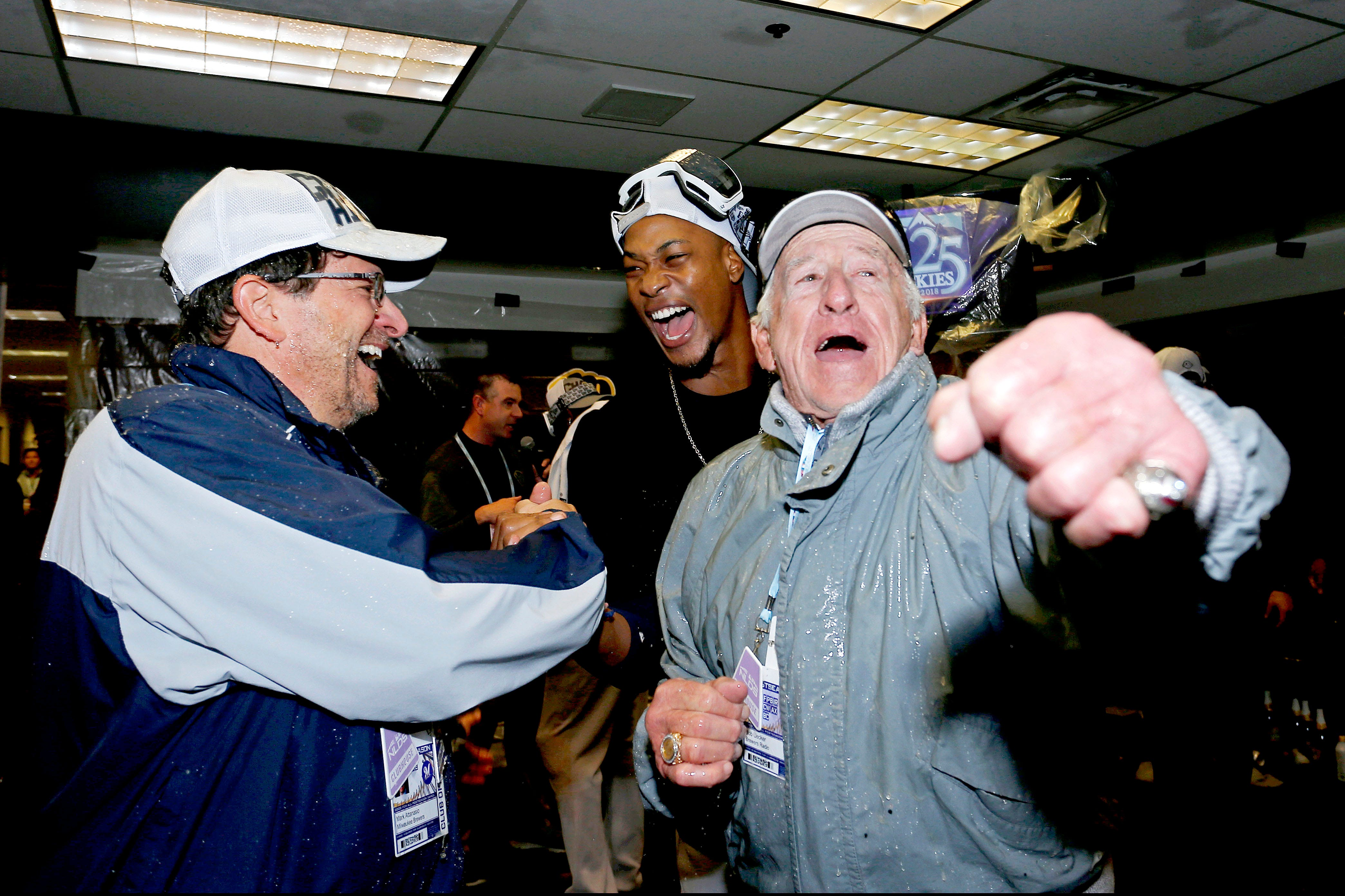 Oct 7, 2018: The Milwaukee Brewers celebrate with broadcaster Bob Uecker after beating the Colorado Rockies in game three of the 2018 NLDS playoff baseball series at Coors Field.