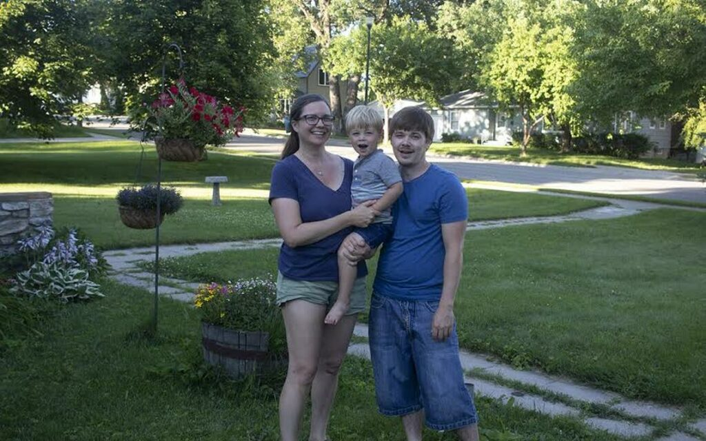 """Bonnie Thompson and Derek Sonnenberg, with their two-year-old son outside their home in Detroit Lakes. The couple founded an indie gaming business in 2018, and are finding success with their latest retro game, """"Sonar Smash."""" (Submitted Photo)"""
