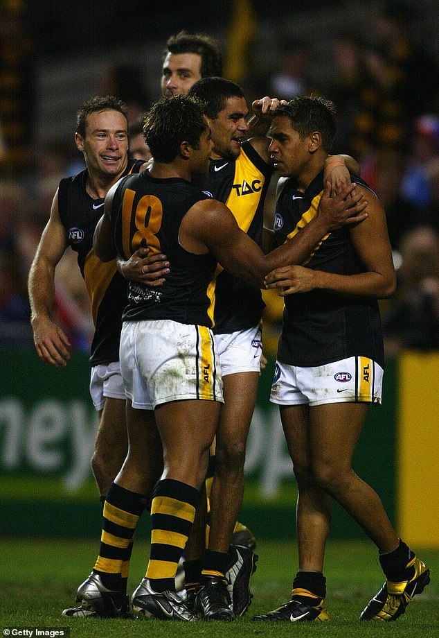 Martin McGarth (pictured centre congratulating a teammate during an AFL game in 2003) played for the Richmond Tigers during his short-lived AFL career