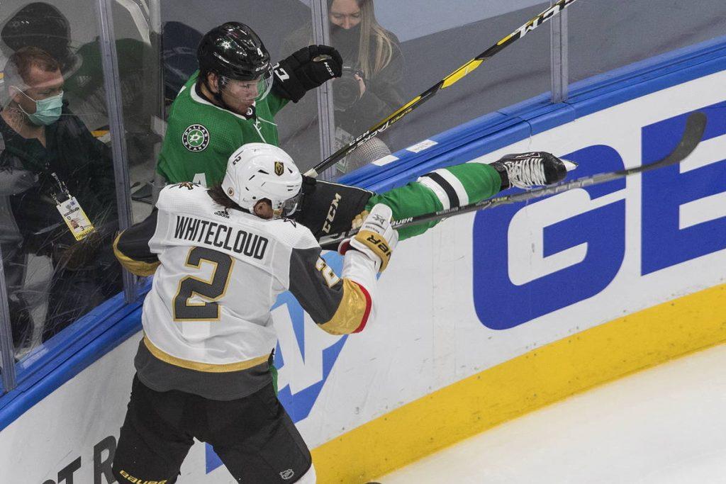 Dallas Stars' Miro Heiskanen (4) is checked by Vegas Golden Knights' Zach Whitecloud (2) during ...