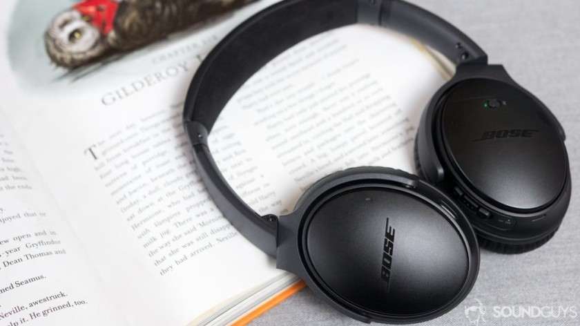 Bose QuietComfort II headphones leaning against an open notebook.