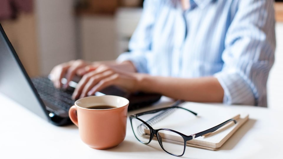 A woman works on a laptop.  A cup of coffee and glasses are in the foreground.